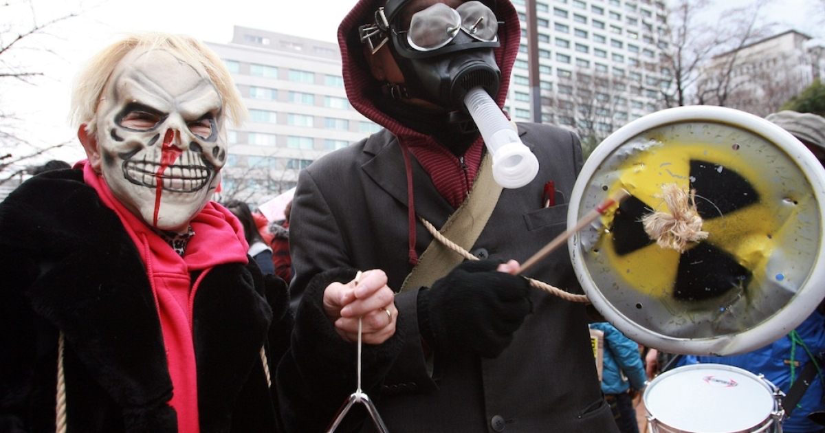 Anti-nuclear protesters wear masks during a demonstration outside Tokyo Electric Power Company's headquarters in Tokyo on March 11, 2012, on the first anniversary of the earthquake and tsunami which triggered a meltdown at the company's Fukushima Daiichi nuclear power plant.</p>