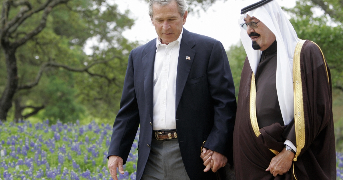 An Apr. 25, 2005 file photo shows U.S. President George W. Bush (L) holding hands with then Saudi Arabian Crown Prince Abdullah as they walk past blue bonnets at Bush's ranch in Crawford, Texas.</p>