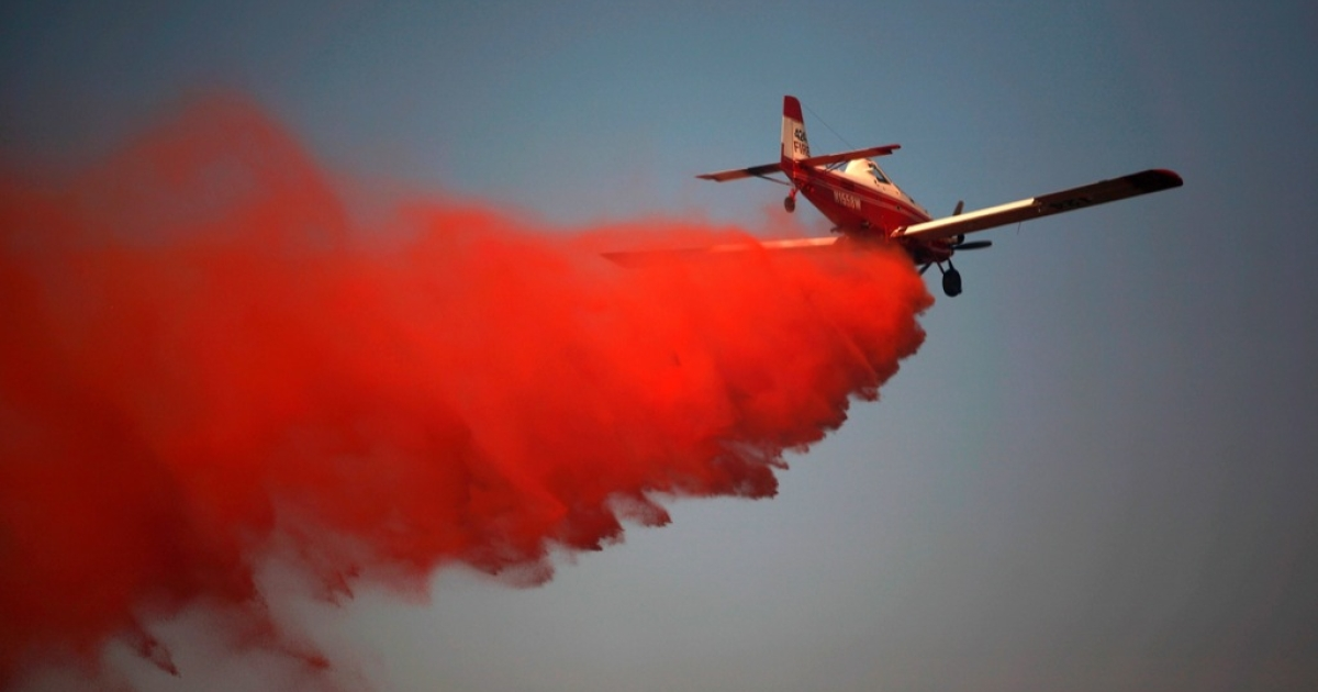 A tanker airplane drops fire retardant on a wildfire on September 1, 2011 in Graford, Texas. More than 6,500 acres and more than 45 homes in the area have burned since Tuesday.</p>