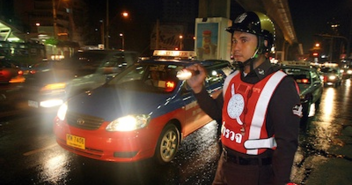 Thai policemen inspecting vehicles at a late-night traffic checkpoint in Bangkok, Thailand in 2003.</p>