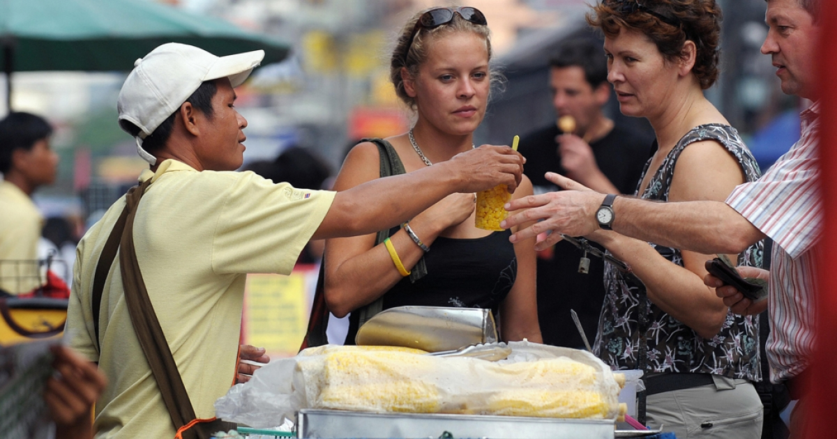 In this picture taken on November 11, 2008, foreign tourists buy a corn snack from a food vendor at Khao San Road, one of Bangkok's main tourist hub.       AFP PHOTO/Christophe ARCHAMBAULT</p>