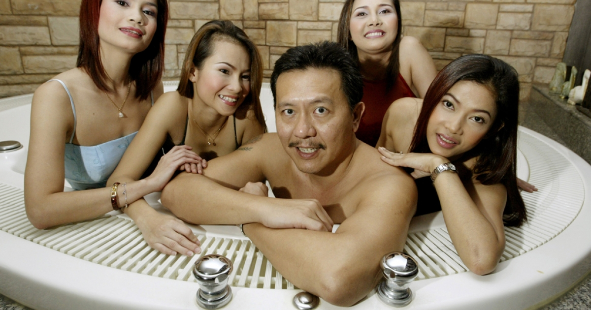 Thailand's massage parlour tycoon Chuwit Kamolvisit (C) poses in a jacuzzi inside Copa Cabana, one of his six upscale entertainment clubs<br />in Bangkok on August 2, 2003.</p>