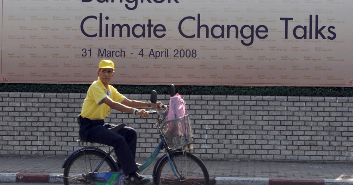 A man rides past by a banner in front of the United Nations building in Bangkok on March 30, 2008, on the eve of an earlier U.N. climate warming conference.</p>