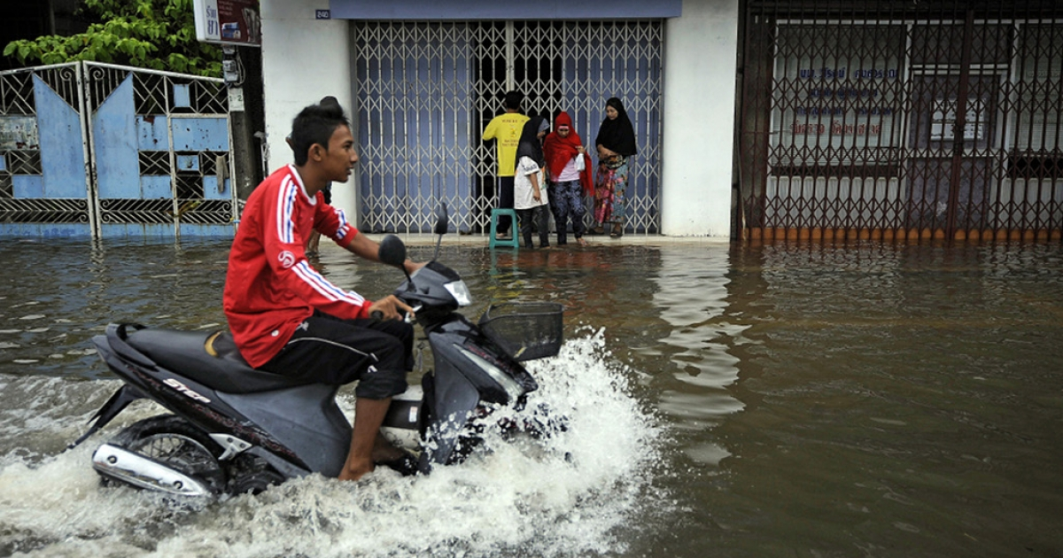 A Thai man rides his motorbike down a flooded street following heavy rains in Thailand's southern city of Narathiwat on March 29, 2011.</p>