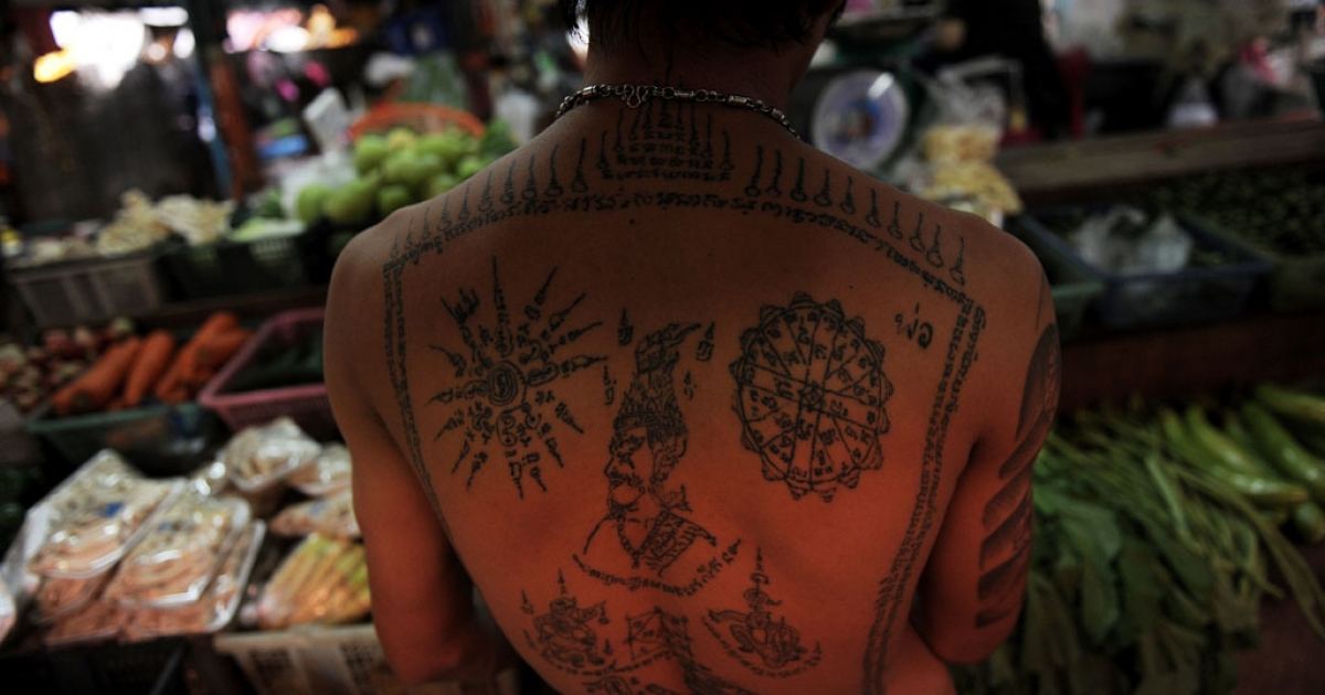 A Thai stall employee with a tattooed back arranges vegetables at a market in downtown Bangkok on March 9, 2011.</p>