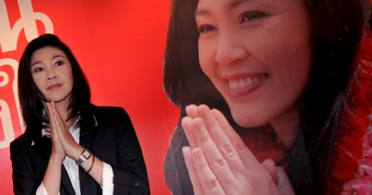 Yingluck Shinawatra, of the opposition Puea Thai party and sister of fugitive Thai ex-prime minister Thaksin Shinawatra, gives a traditional greeting next to a large portrait of herself during a press conference at her party headquarters in Bangkok on July 3, 2011. Puea Thai had won a majority of seats in Parliament, paving the way for Yingluck to be the nation's first female prime minister.</p>