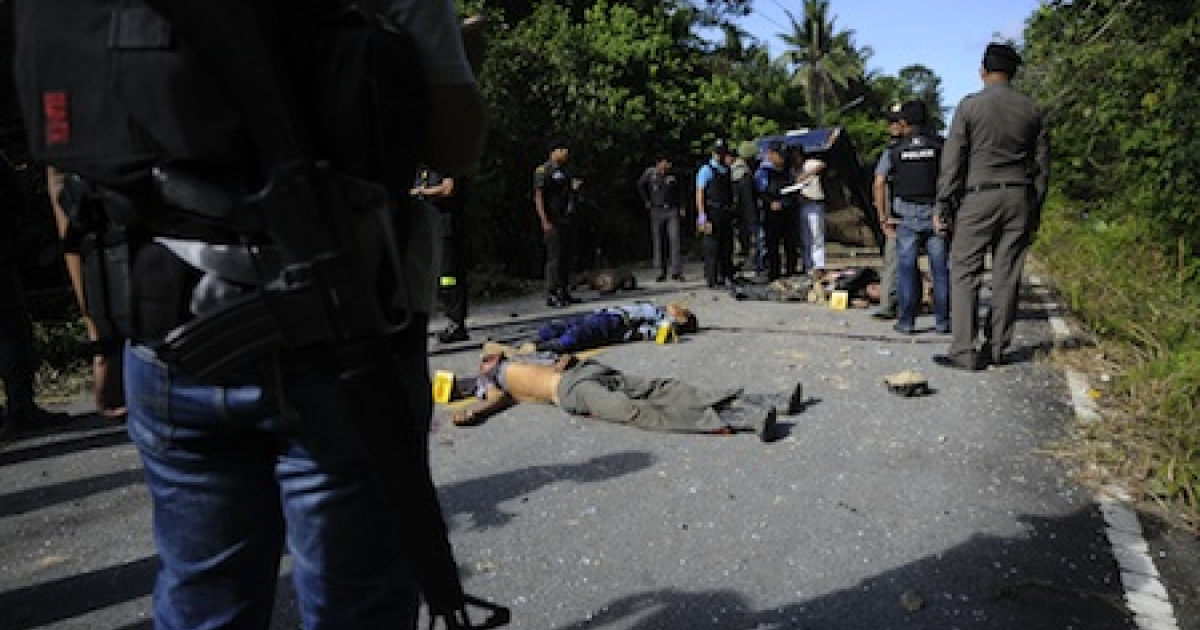 Thai police officers inspect the bodies of six Thai Buddhist hunters, shot dead by suspected separatist Muslim militants following a roadside bomb blast in Thailand's restive southern province of Narathiwat on November 2, 2011.</p>