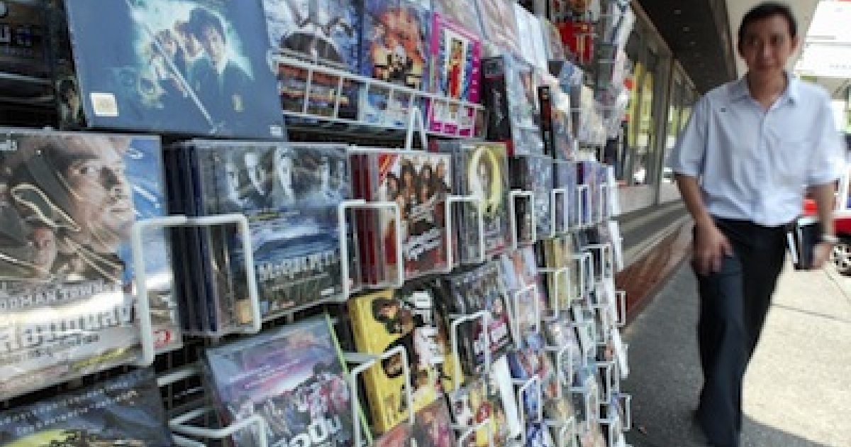 A stall selling pirated CDs and movies in Bangkok, Thailand.</p>