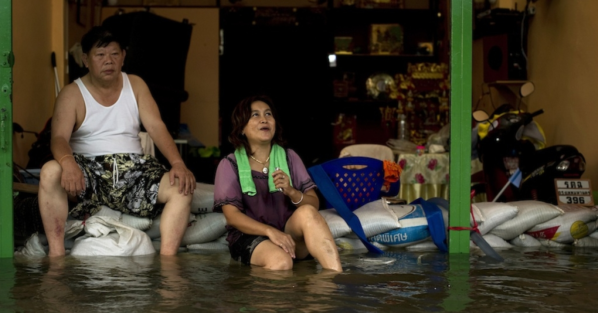 Local residents sit on sandbags in front of their shop surrounded by flood waters after a mud and sandbag wall collapsed in Bang Bua Thong in Nonthaburi province, suburban Bangkok, on Oct. 19, 2011.</p>