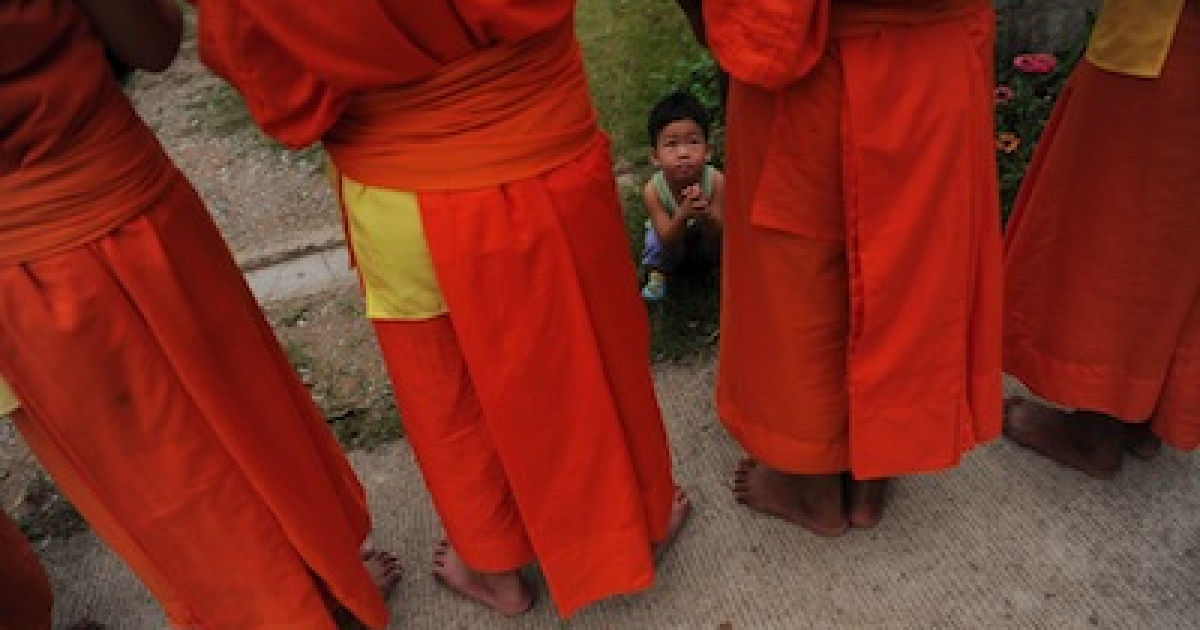 A young boy watching Buddhist monks in Thailand's northern border town of Chiang Khong.</p>