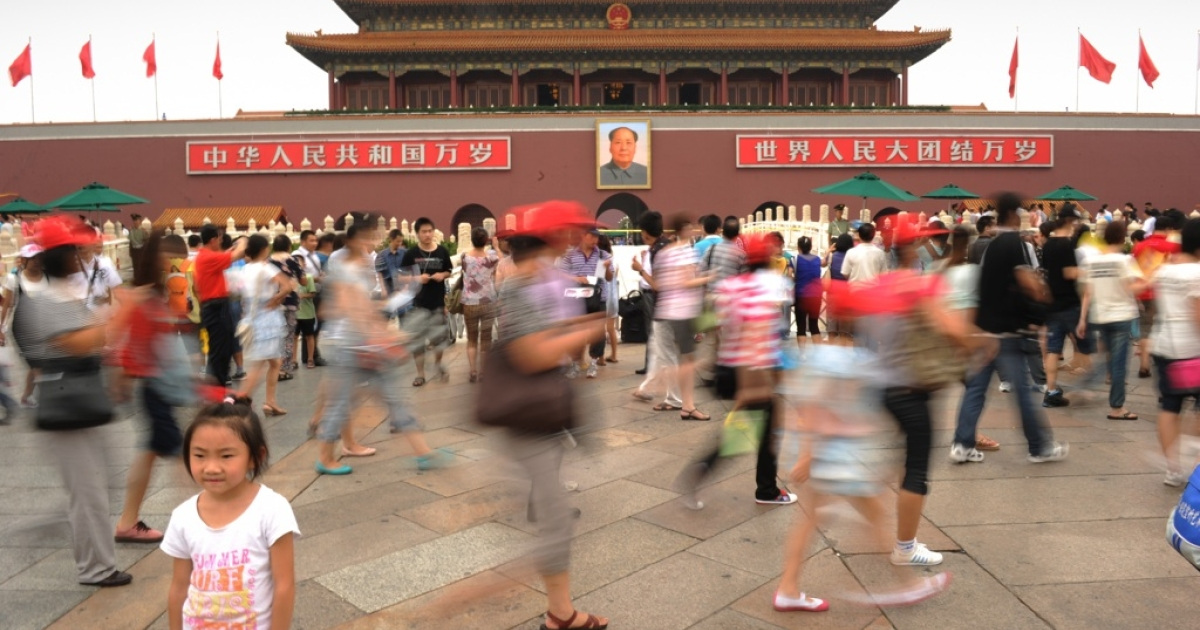 Visitors have their photos taken in Tiananmen Square in Beijing on August 17, 2011.</p>