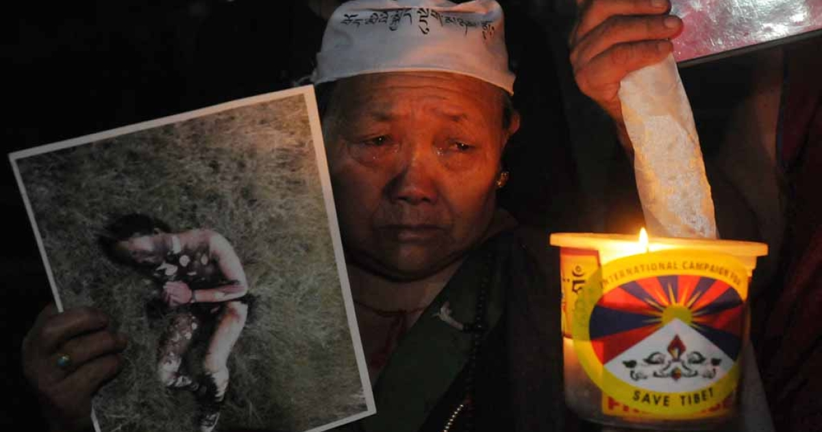 An exiled Tibetan woman holds a photograph of a Tibetan youth who self-immolated during a candlelight vigil in McLeod Ganj, Dharamsala, on Sept. 30, 2012. The youth in the photo, from eastern Tibet, allegedly burned himself in protest against Chinese rule on Sept. 29.</p>