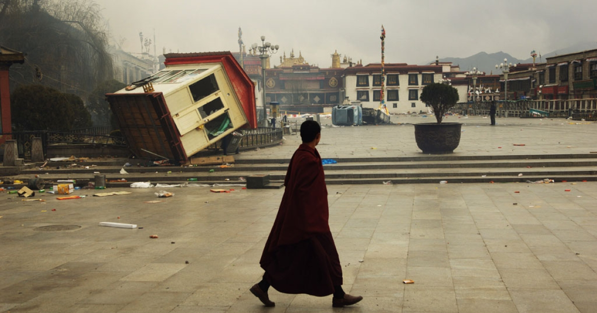 A Tibetan monk walks past an overturned barrack in Lhasa, the capital of the Tibet Autonomous Region, on March 14, 2008.</p>