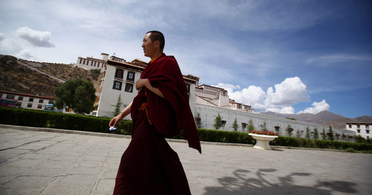 A Tibetan Buddhist monk walks on the Potala Palace square on June 19, 2009 in Lhasa, Tibet Autonomous Region, China.</p>