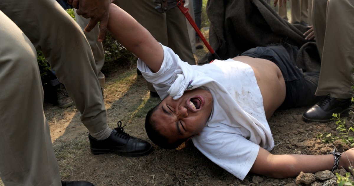 A lone protester is dragged away by Indian police moments after he tried to set himself on fire in front of the Chinese embassy in New Delhi on Nov. 4, 2011.</p>