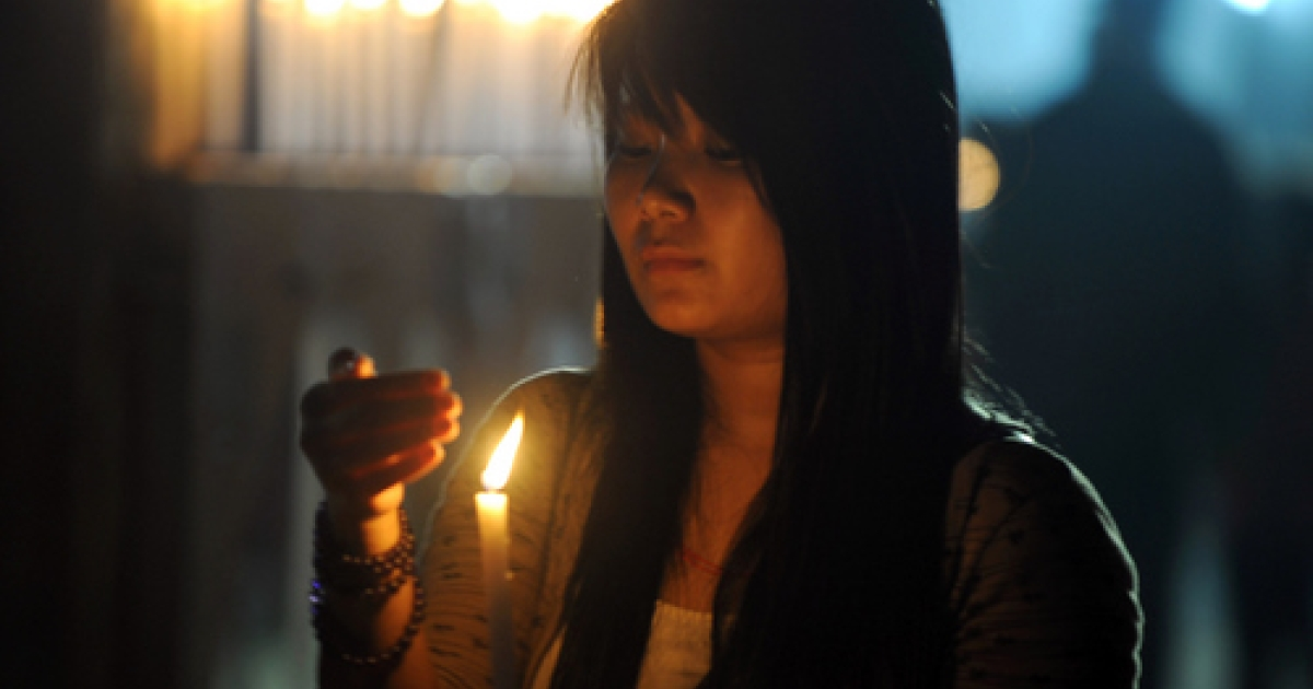 A Tibetan woman attends a candlelight vigil in memory of the self immolations in Tibet during the eighth day of the Kalachakra Festival in Bodhgaya on January 8, 2012.</p>