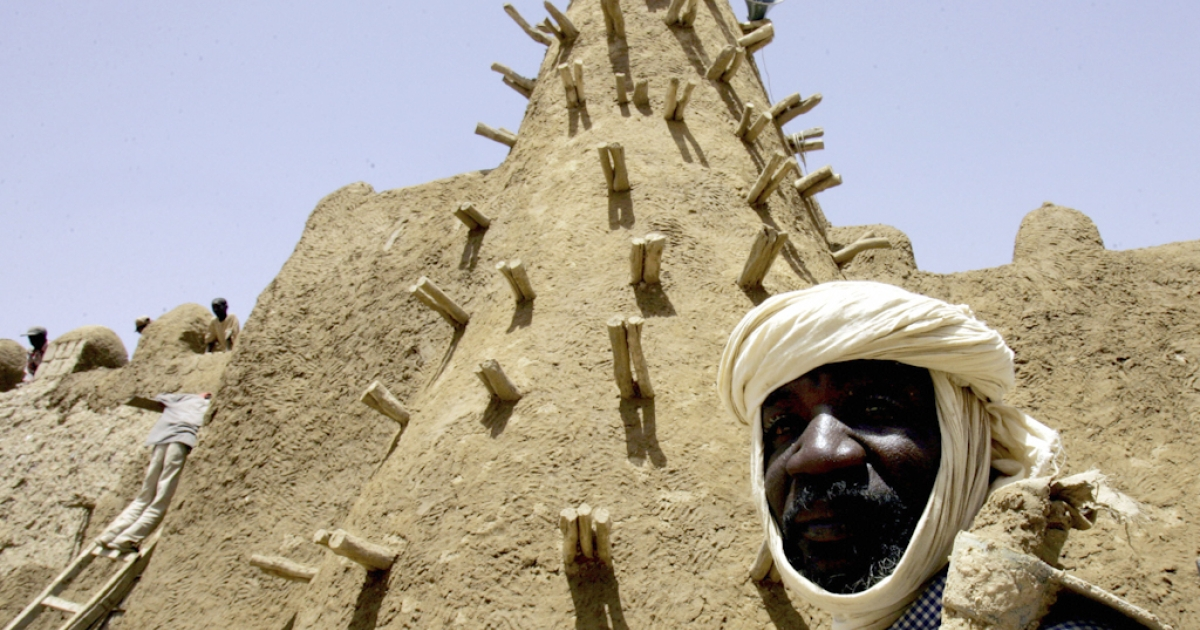A resident of Timbuktu walks past the restored City of 333 Saints' Djingareyber Mosque.</p>