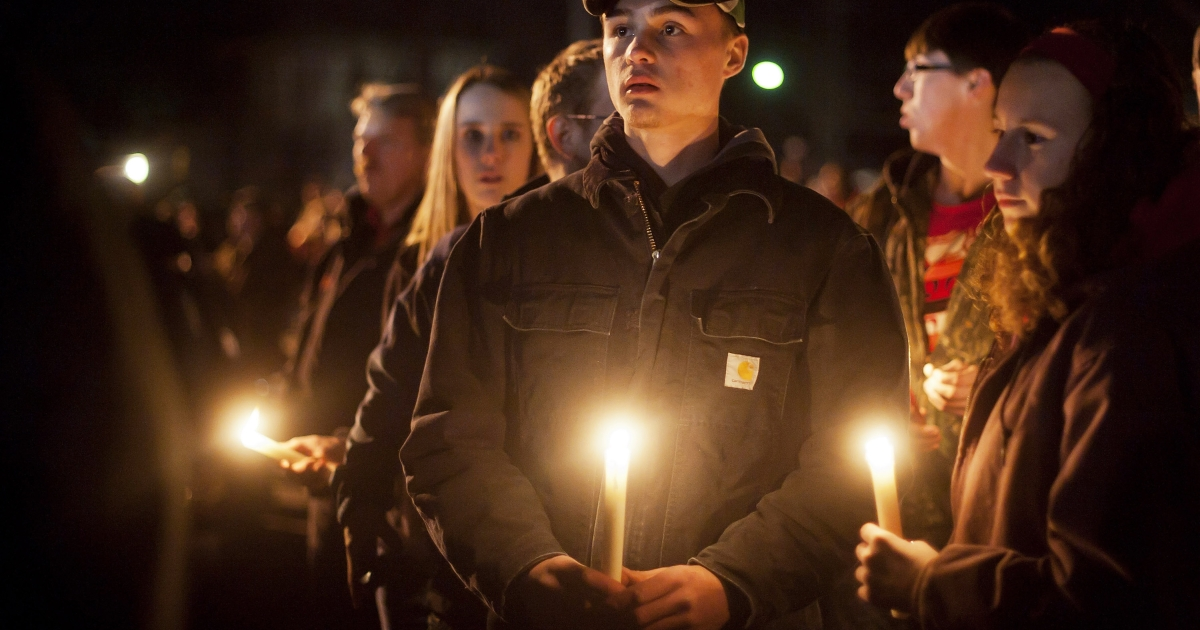 Students and those in the community embrace one another on Tuesday as they hold a candlelight vigil at St Mary's of the Assumption Church in Chardon, Ohio.</p>