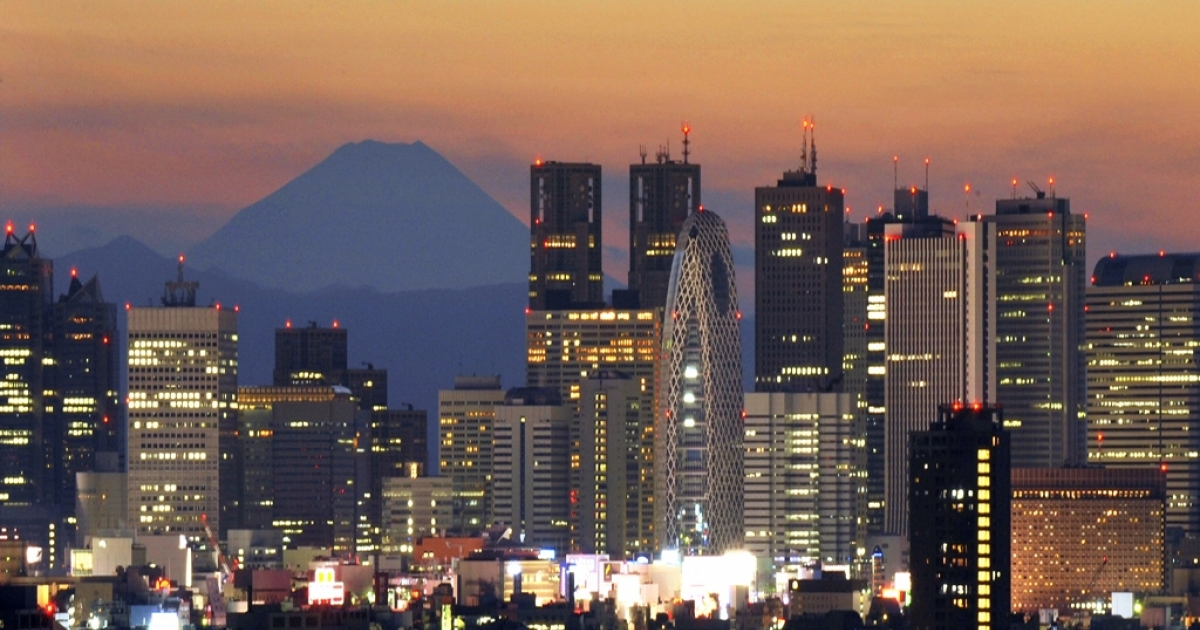 This file photo shows Japan's highest mountain Mount Fuji rising up behind the skyscraper skyline as the sun sets over Tokyo.</p>