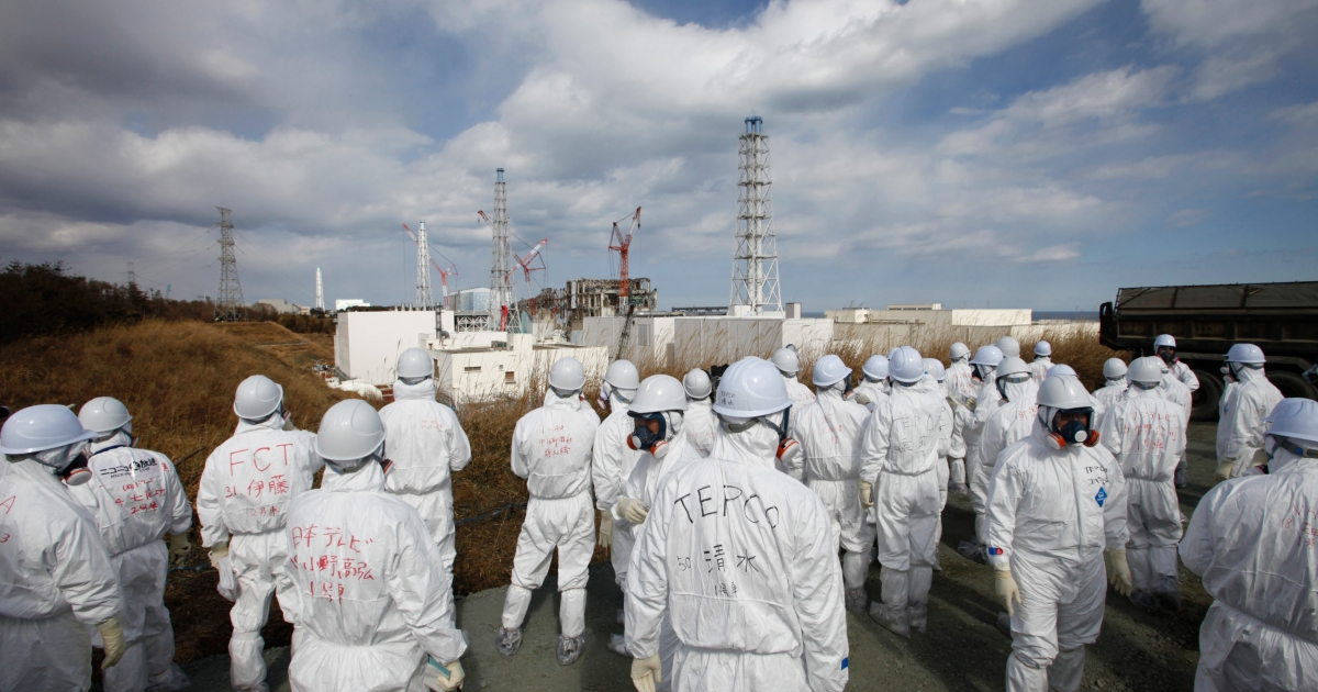 Members of the media wearing protective suits and masks are escorted at the Tokyo Electric Power Company's tsunami-crippled Fukushima Daiichi nuclear power plant on Feb 20.</p>