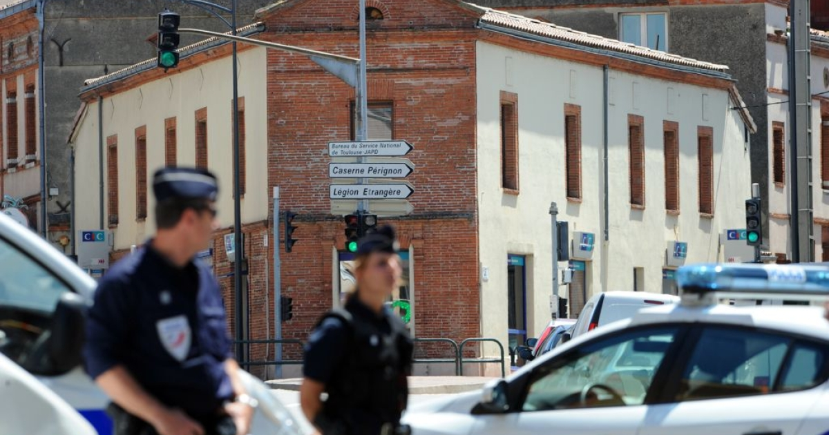 Police stand outside the CIC bank in Toulouse, in the south of France, where four people have been taken hostage by a man claiming to belong to Al Qaeda.</p>