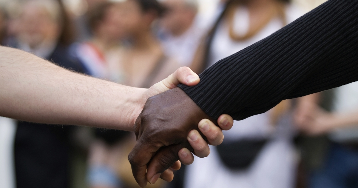 A white person and a black person hold hands as they take part in a march in Paris today. The march was called by human rights organizations following the serial murders in the Midi-Pyrénées region this month in which an Islamic extremist, since killed, was the suspected culprit.</p>