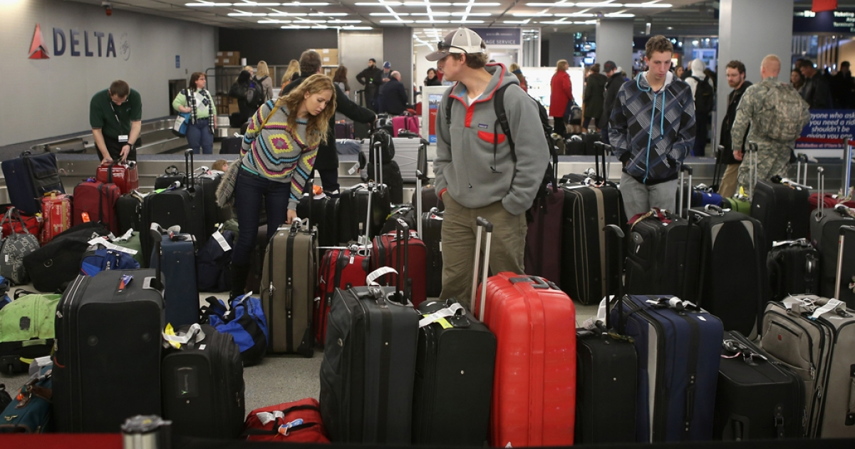Passengers arriving at O'Hare International Airport search for their luggage on Dec. 21, 2012, in Chicago, Ill. Trakdot, one of the many gadgets from this year's Consumer Electronics Show, helps alleviate travel stress by texting passengers when their bags have arrived.</p>