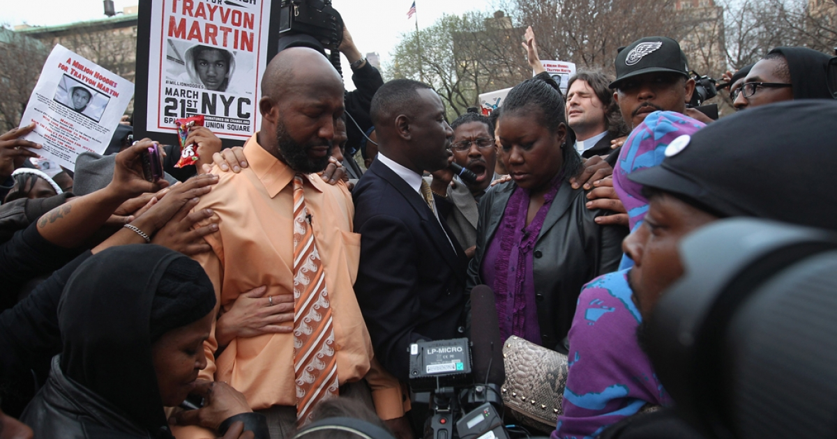 Tracy Martin (left in orange shirt), and Sybrina Fulton,(R), parents of slain teenager Trayvon Martin, pray at a Million Hoodies March on March 21, 2012 in New York City. The family members joined hundreds of protesters calling for justice in the killing of Trayvon Martin, 17, who was was pursued and shot on February 26 in Sanford, Florida by
