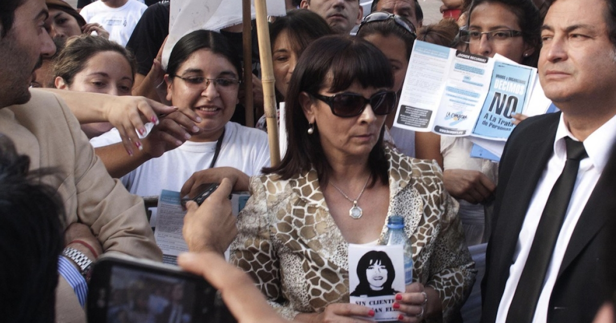 Susana Trimarco (C), mother of disappeared Maria de los Angeles 'Marita' Veron, holds her portrait as she enters the Court in Tucuman, Argentina, on December 11, 2012. The 13 people accused of the kidnapping of Veron were found not guilty, prompting mass protests and at least one political resignation.</p>