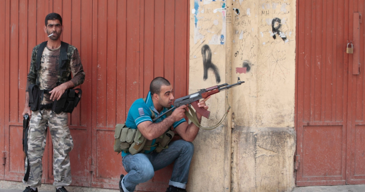Fighters are seen during fighting in the Bab al-Tebbaneh neighborhood of the northern Lebanese city of Tripoli after clashes broke out between factions supporting and opposed to the revolt in Syria on May 13, 2012.</p>