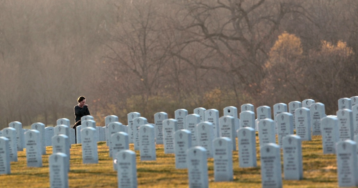 A Veterans' Day visitor to Abraham Lincoln National Cemetery stops to reflect at a grave on November 11, 2010, in Elwood, Illinois.</p>