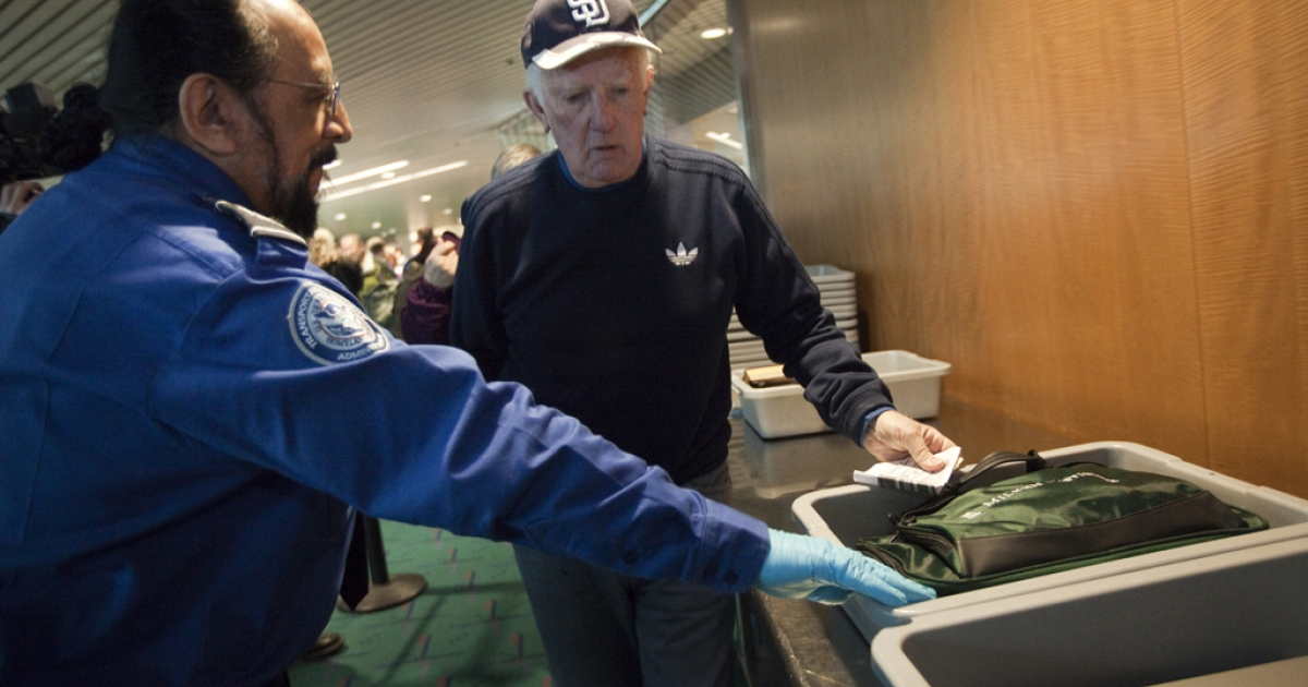 Transportation Security Administration (TSA) officer Stephen Candia helps a patron pass though a security check. Several current and former TSA agents at LAX have been indicted for allegedly taking bribes to allow drug shipments through security.</p>