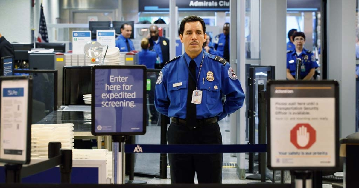 A TSA agent waits for passengers to use the TSA PreCheck lane being implemented by the Transportation Security Administration at Miami International Airport on October 4, 2011 in Miami.  (Photo by Joe Raedle/Getty Images)</p>