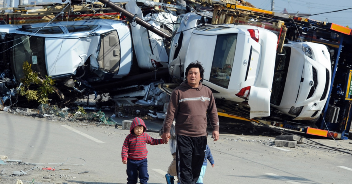 Residents walk past cars upturned by the tsunami to the east of Sendai in Miyagi prefecture on March 13, 2011.</p>