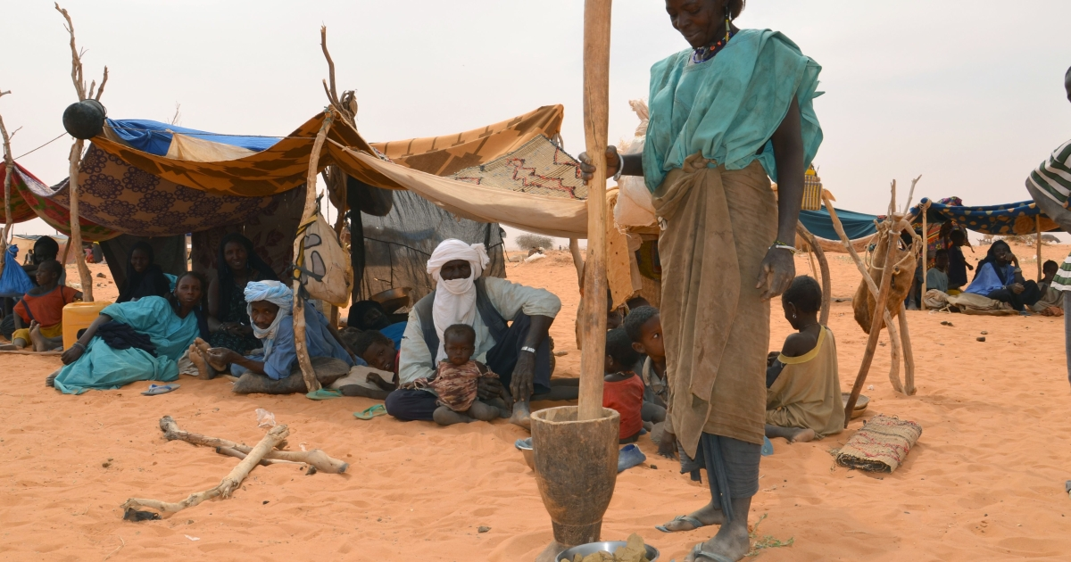A woman prepares a meal at a Malian refugee camp in Chinegodar, western Niger, close to the Malian border.</p>