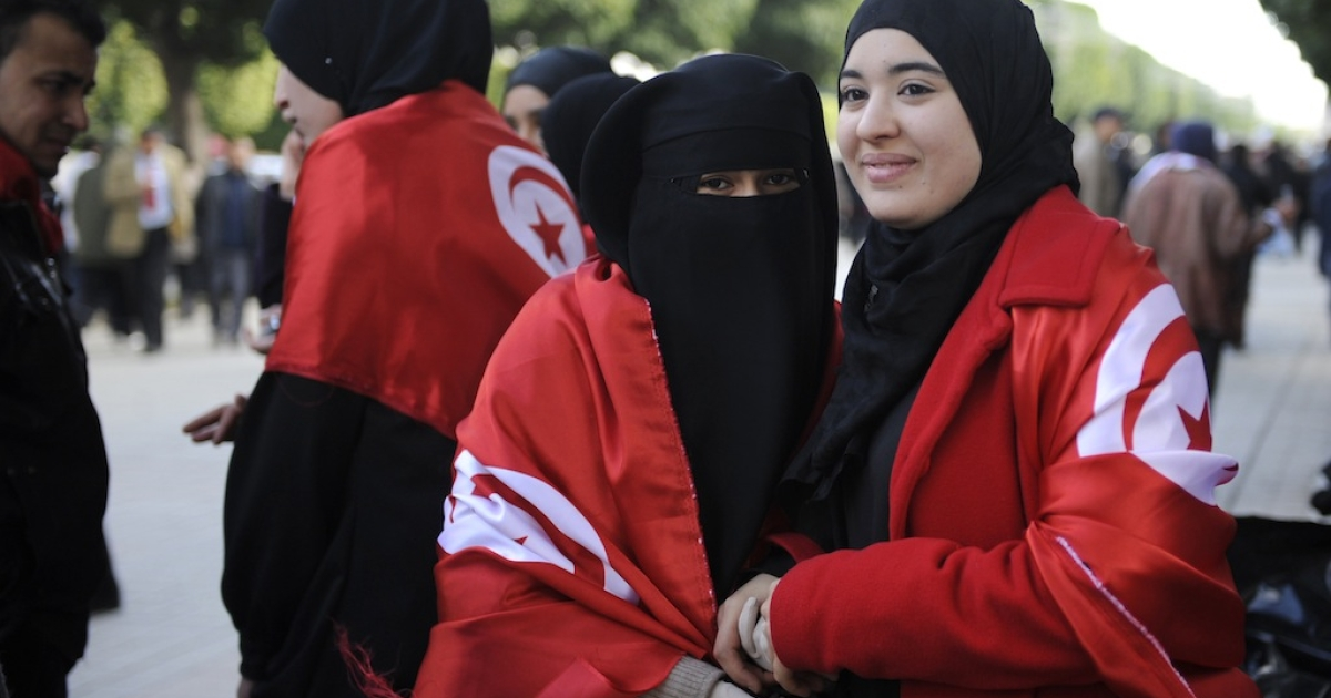Tunisian women wrapped in Tunisian flags pose during a demonstration to demand jobs and dignity as the north African country marks a year to the day since its despot Zine El Abidine Ben Ali fled into exile on January 14, 2012 on Habib Bourguiba Avenue in Tunis. Some demonstrators, wearing the red and white of the national flag, called for recognition of the 'martyrs' killed during the weeks of unrest before Ben Ali was toppled.</p>