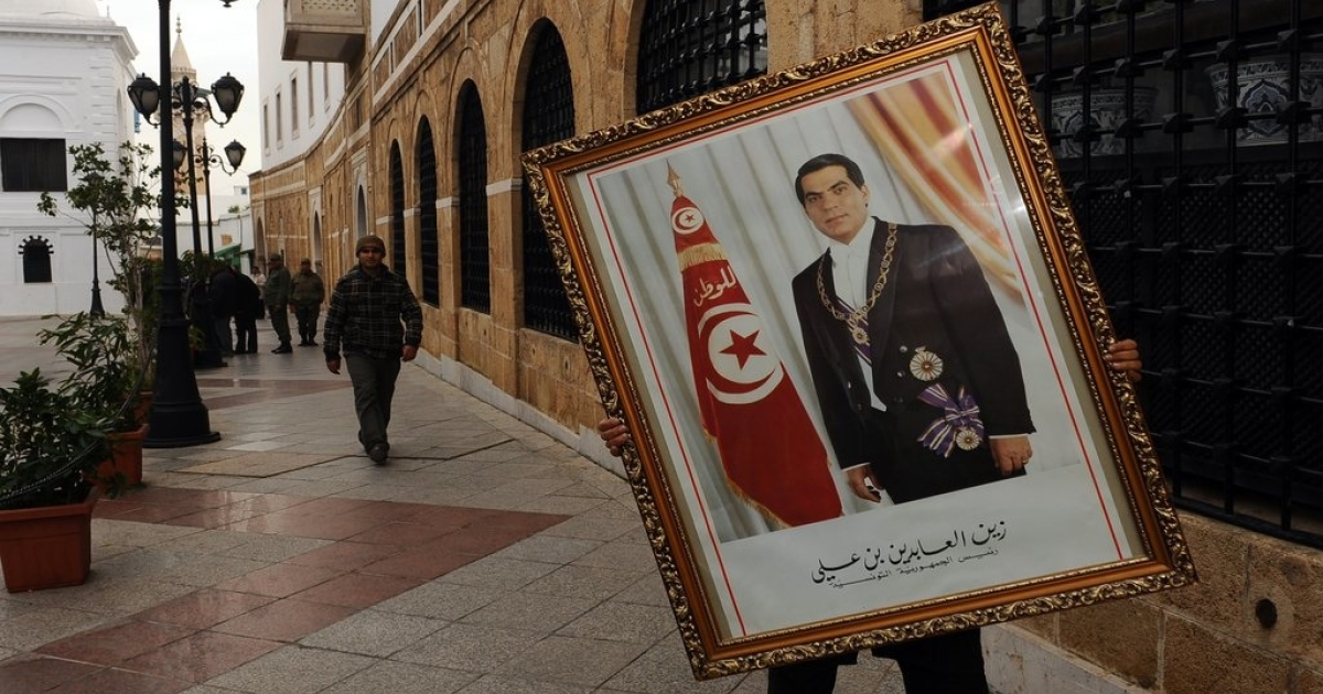 A Tunisian government employee carries a picture of ex-president Zine al-Abidine Ben Ali, who resigned from office after weeks of protests against poverty and corruption in January, igniting the