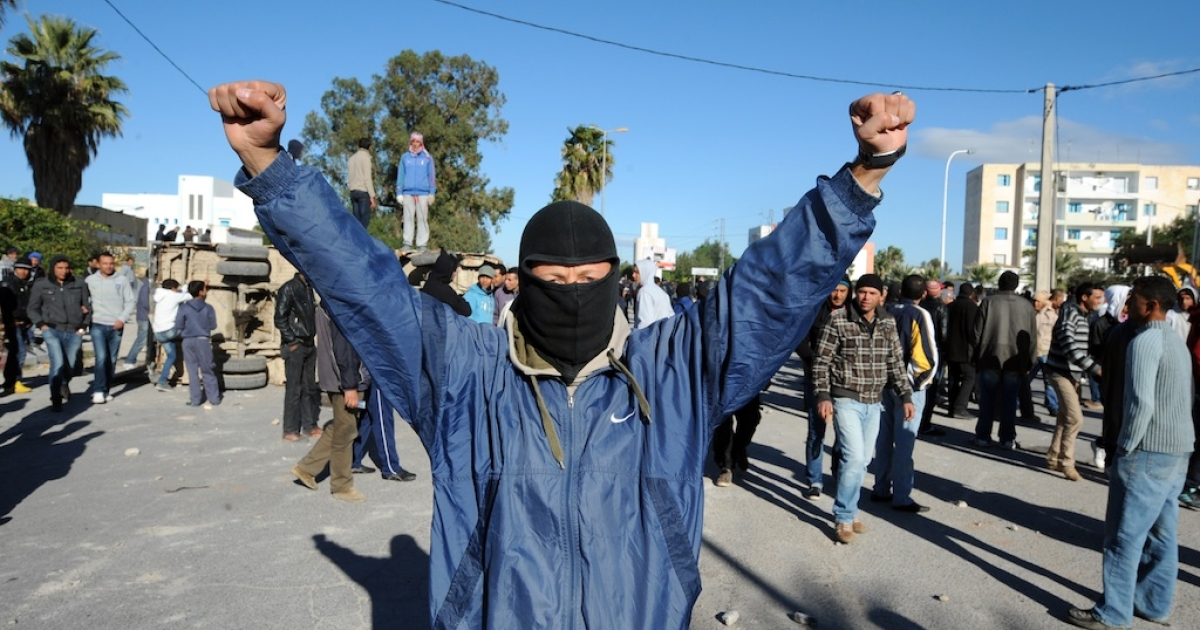 A Tunisian protester raises his arms during clashes with security forces in the southern town of Siliana, on November 29, 2012. More than 250 people were wounded in a second day of clashes between Tunisian security forces, a hospital source told AFP, as they called for the resignation of Ahmed Ezzine Mahjoubi, the governor of Siliana, a poor farming region 120 kilometres (75 miles) south of Tunis.</p>