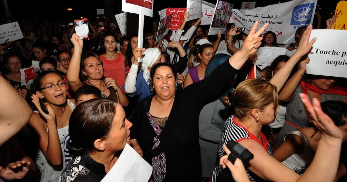 Tunisian women shout slogans and hold posters reading, 'don't touch my rights' and 'woman is the future of man' during a protest calling for the respect of women's rights and other fundemental rights on August 13, 2012 in Tunis.</p>