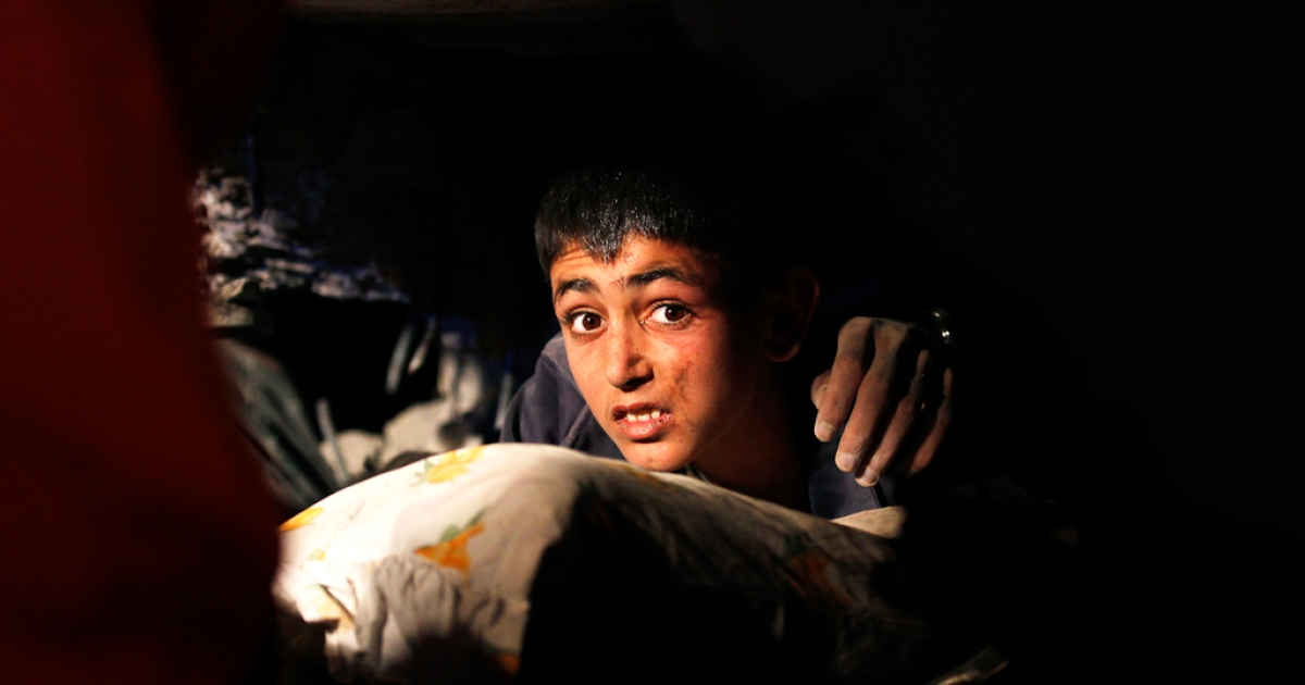 Yunus, a 13-year-old earthquake survivor with a hand of a victim on his shoulder, waits to be rescued from under a collapsed building by rescue workers in Ercis, near the eastern Turkish city of Van. Oct. 24, 2011.</p>