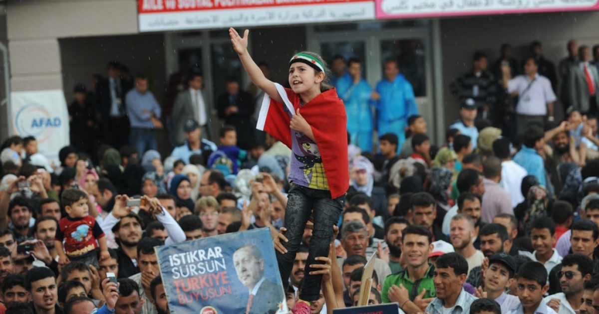 Syrian refugees dance and chant slogans before Turkish Prime Minister Recep Tayyip Erdogan`s arrival on May 6, 2012 at the Oncupinar Refugee Camp in the border town of Kilis, in southeastern Turkey.</p>