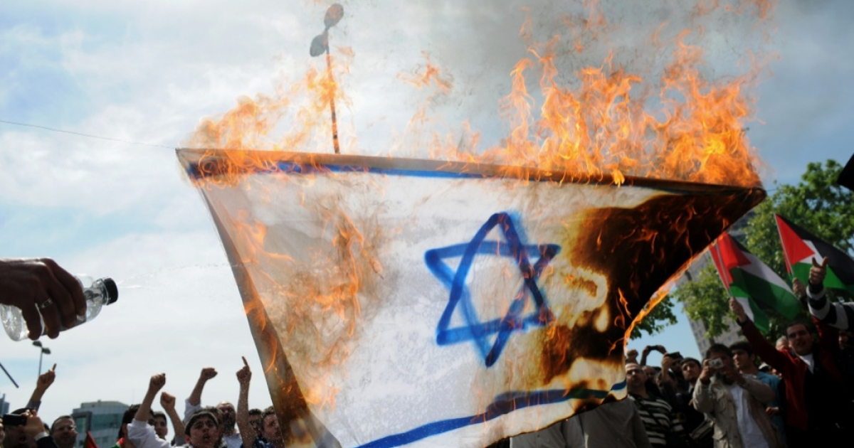 Protestors burn an Israeli flag as they chant anti-Israel slogans during a demonstration in front of the Israeli consulate on May 15, 2011 in Istanbul.</p>