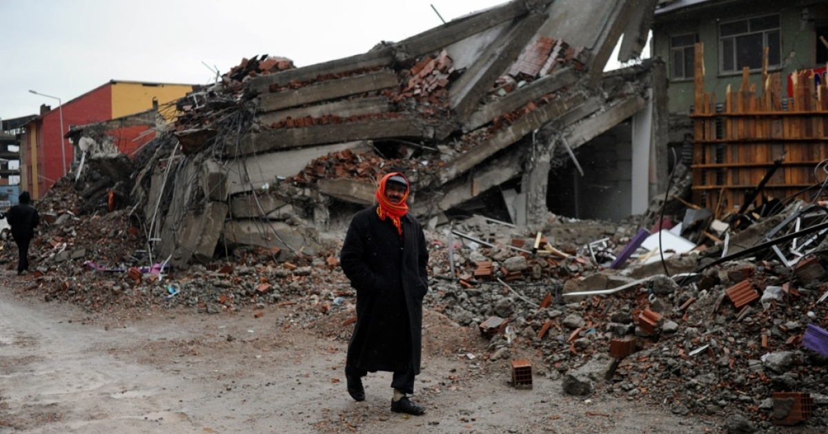 A homeless survivor walks by a collapsed building in Ercis.</p>