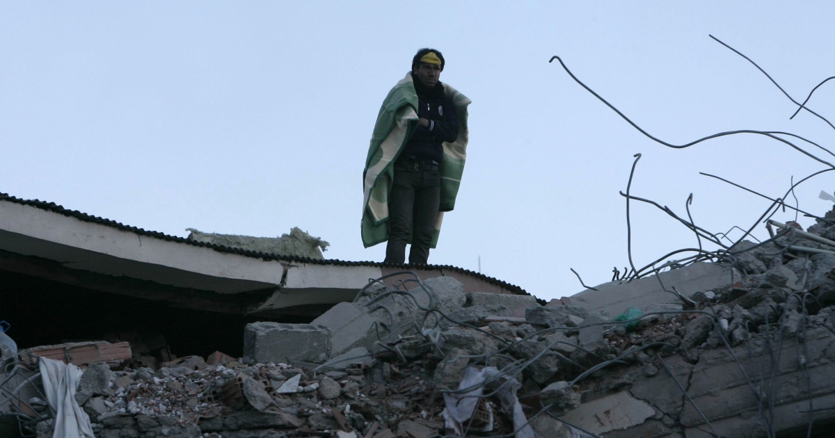 A quake survivor stands amid the rubble of a building in Van, eastern Turkey, on Oct. 24, 2011.</p>