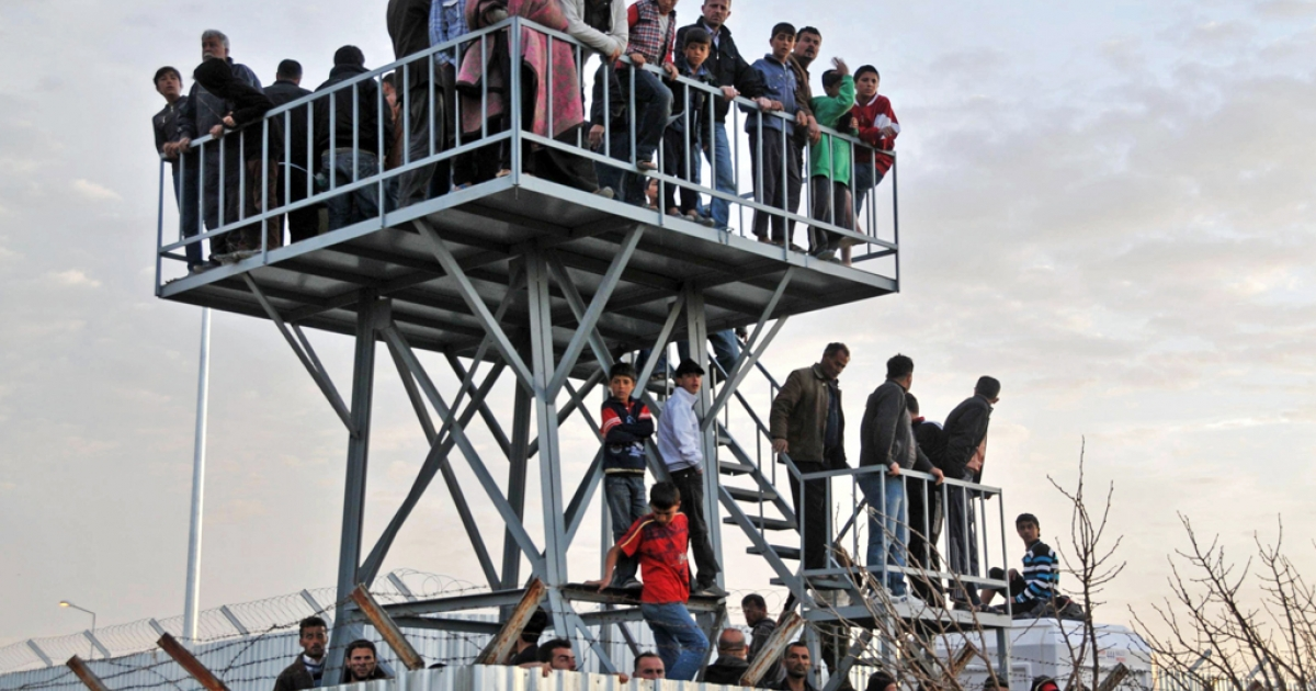 Syrian refugees in Turkey watch the border from Oncupinar Refugee Camp on April 9, 2012.</p>