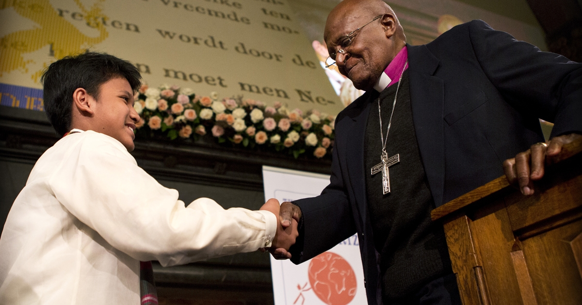 South African Archbishop Desmond Tutu shakes hands with Philippine's Philippine Kesz, 13, after awarding him with the Children's Peace Prize at the Ridderzaal in the Hague on September 19, 2012. A</p>