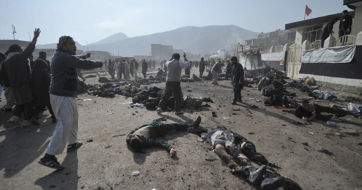 Afghan men cry as they try remove the bodies and help wounded people after explosions during a religious ceremony in the centre of Kabul on December 6, 2011.</p>