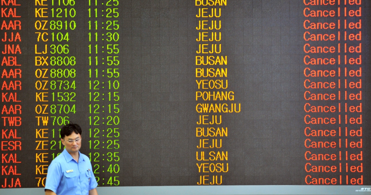 A man walks past an airport board announcing that all flights are cancelled following major typhoon Bolaven at Seoul domestic airport in Seoul on August 28, 2012. The state weather agency issued a typhoon warning on early August 28, 2012 for Seoul, the capital of about 10 million people, as the storm named Bolaven continued moving northwards.</p>