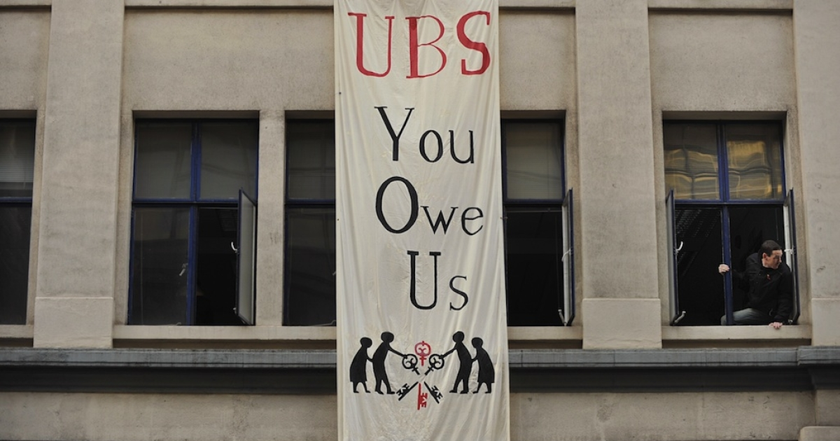 Anti-capitalist activists hang banners on the outside of an empty office block owned by Swiss banking giant UBS in London on November 18, 2011.</p>