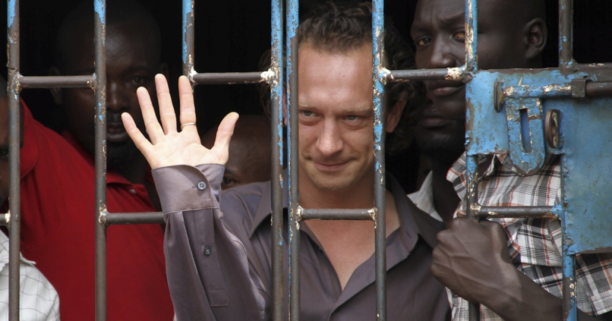 British theatre producer David Cecil waves from a court cell at the Makindye Court on September 13, 2012 in kampala, after being arrested for staging a play about a gay man despite a temporary ban by the country's media authorities. The groundbreaking play, titled